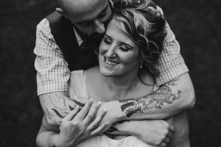 Groom with tattoos embraces bride from behind on their wedding day
