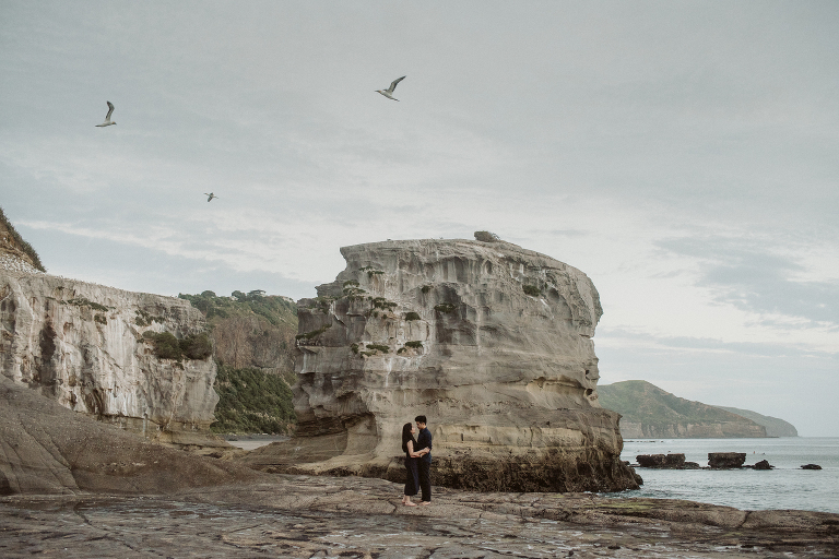 A couple embrace next to the rocks at the gannet colony at Muriwai Beach on the West Coast of Auckland