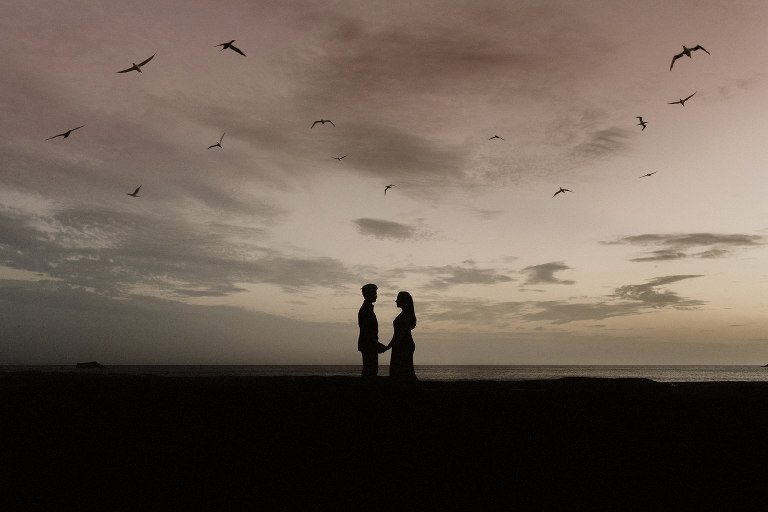 A silhouette of a couple with birds flying above them on the rocks at Muriwai Beach in Auckland