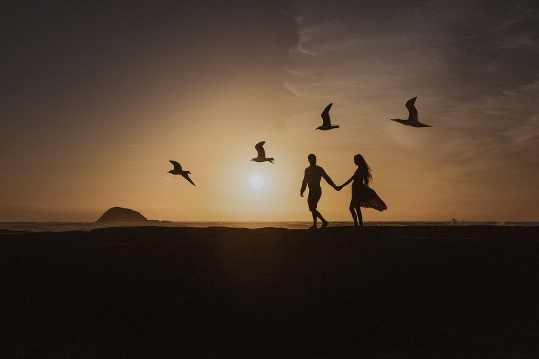 A silhouette of a couple walking along Muriwai Beach in Auckland at sunset with birds from the gannet colony flying overhead